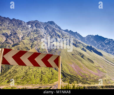 Road sign 'A sharp turn' on the road in the highlands. - Stock Photo