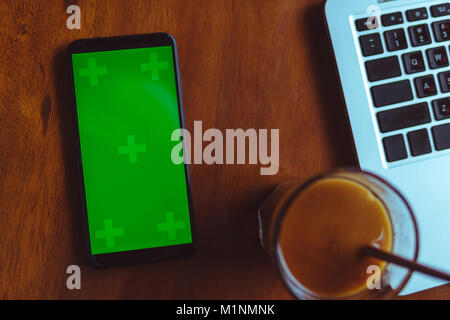 Office desk table with laptop, smartphone with green screen and coffee - Stock Photo