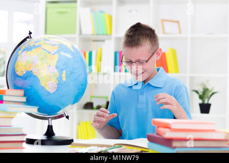 A sad and tired boy sitting at the desk  with a pile of books - Stock Photo