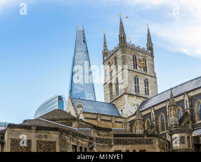 New property contrasted to old: historic Southwark Cathedral tower against the iconic tall modern Shard skyscraper - Stock Photo