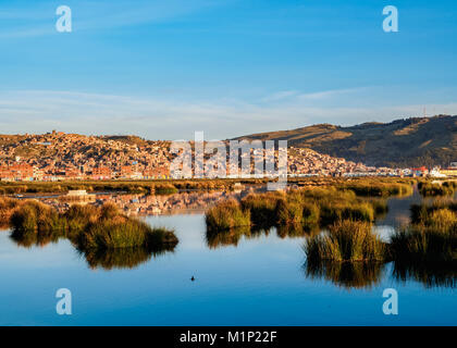 Lake Titicaca and cityscape of Puno at sunrise, Peru, South America - Stock Photo