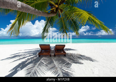 Two deck chairs under palm trees and tropical beach, The Maldives, Indian Ocean, Asia - Stock Photo