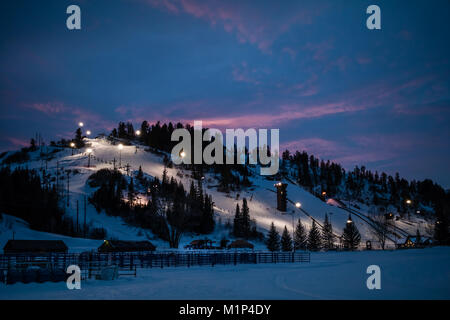 Beautiful view of of a downhill slope lit for night skiing in Steamboat Springs, Colorado, after sunset - Stock Photo