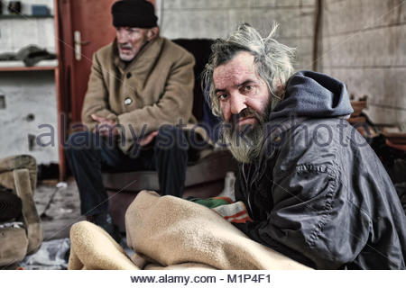 Homeless men sitting in abandoned house - Stock Photo