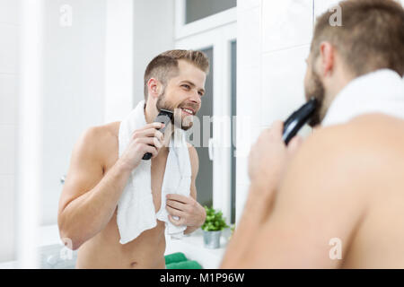 Handsome young bearded man trimming his beard with a trimmer - Stock Photo