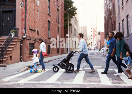 Two families with daughters crossing road - Stock Photo