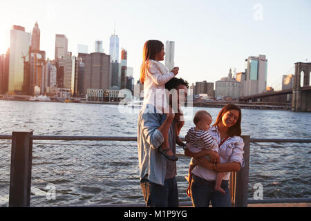 Young family with daughters standing on quayside, side view - Stock Photo