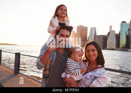Young family with daughters standing on quayside, close up - Stock Photo
