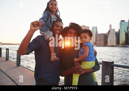 Young family with daughters standing on quayside - Stock Photo