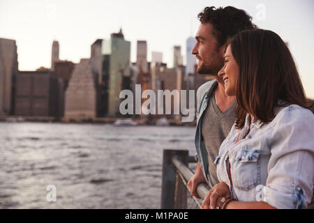 Two young couples standing on quayside, front view - Stock Photo