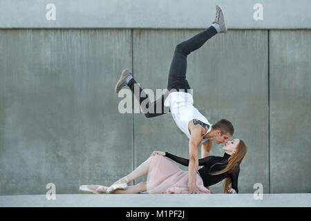 Slender ballerina dances with a modern dancer. Dating lovers. Passion and romance of dance. They look into each - Stock Photo