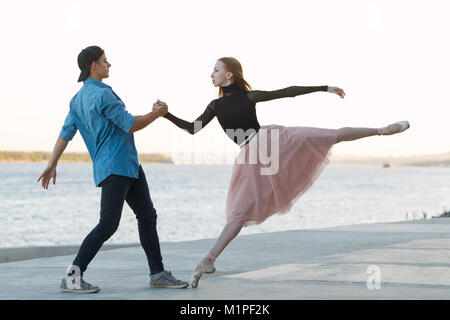 Slender ballerina dances with a modern dancer. Dating lovers. Passion and romance of dance. He holds her hand. Performance - Stock Photo