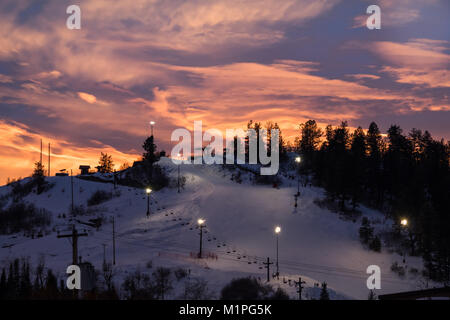 Beautiful view of a ski slope lit for night skiing in Steamboat Springs, Colorado, sunset in the mountains - Stock Photo