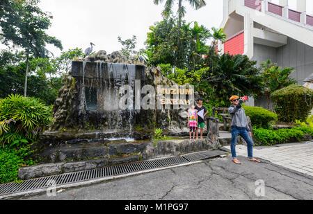 Asian tourists taking a selfie in front of the Muzium Sabah, Kota Kinabalu, Sabah, Borneo, Malaysia - Stock Photo
