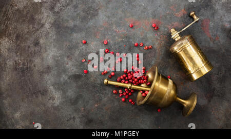 Pink pepper seeds, a brass pepper mill and a mortar on metal rusty background, top view, copy space - Stock Photo