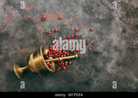 Pink pepper seeds and a brass mortar on metal rusty background, top view, copy space - Stock Photo