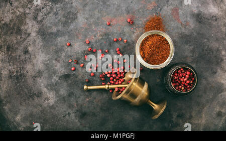 Pink pepper seeds and powder and a brass mortar on metal rusty background, top view, copy space - Stock Photo