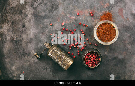 Pink pepper seeds and powder and a brass pepper mill on metal rusty background, top view, copy space - Stock Photo