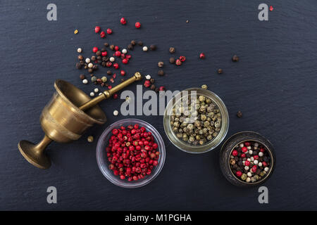 Various pepper seeds and a brass mortar and pestle on black stone background, top view, copy space - Stock Photo