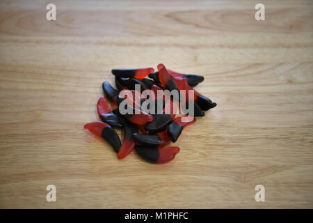 food of sweets treats or candy with red and black liquorice in chili and cherry flavor on wood background - Stock Photo