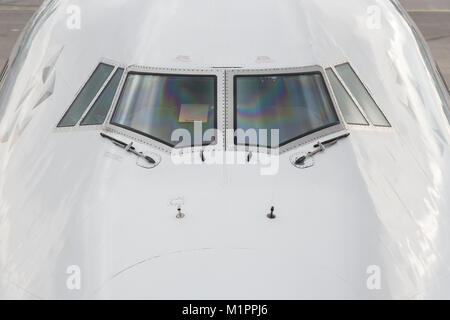 Close up of the front windshield and wipers of a jumbo jet with the airport as a  background. - Stock Photo