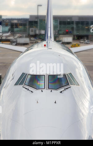 High angle close up of the front windshield and wipers of the jumbo jet nose with the airport as a  background. - Stock Photo