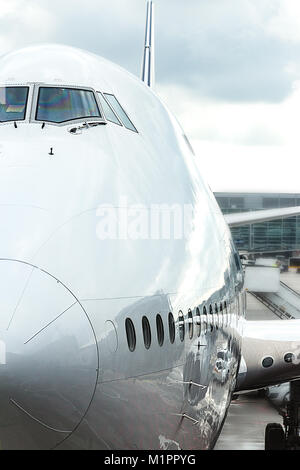 Close up of the front nose of a jumbo jet with the airport as a  background. - Stock Photo