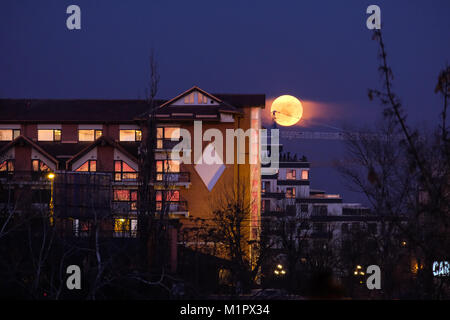 Bucharest, ROMANIA - January 31 2018: Super Blue Blood Moon rising close to Hotel Caro in Bucharest. Rare lunar - Stock Photo