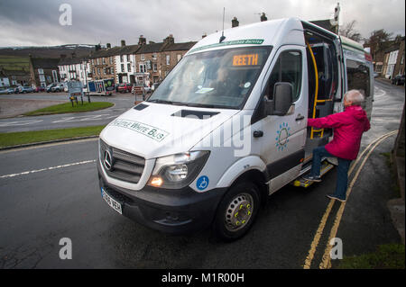 76 yr old Ruth Emerson boards the Little White Bus at Reeth in upper Swaledale to travel to Richmond. - Stock Photo