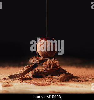 close up view of pouring caramel onto heap made of truffle and chocolate bars on black - Stock Photo