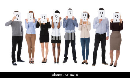 Group Of College Students Hiding Behind Question Mark Sign Against White Background - Stock Photo
