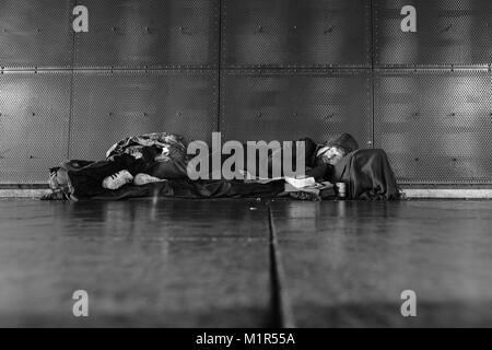 A homeless man sleeps on the hard cold concrete floor under Leeds Railway Station - Stock Photo