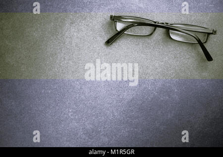 closed eyeglasses on a dark stone surface - top view - Stock Photo