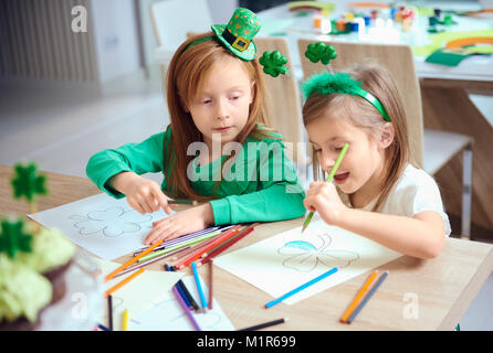 Cheerful siblings coloring different illustrations - Stock Photo