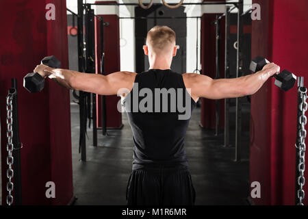 Rear View Of Young Man Getting Trained With Dumbbell In Gym - Stock Photo