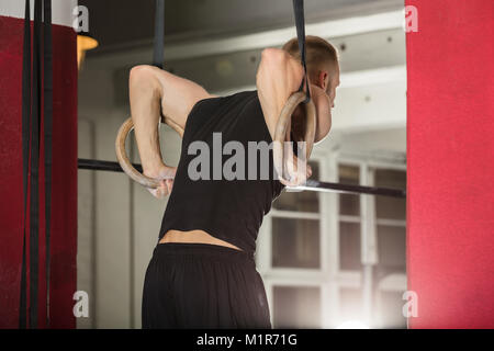 Young Fit Man Pulling Up On Gymnastic Rings In The Gym - Stock Photo