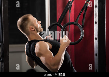 Fitness Man Pulling Up On Gymnastic Rings In The Gym - Stock Photo
