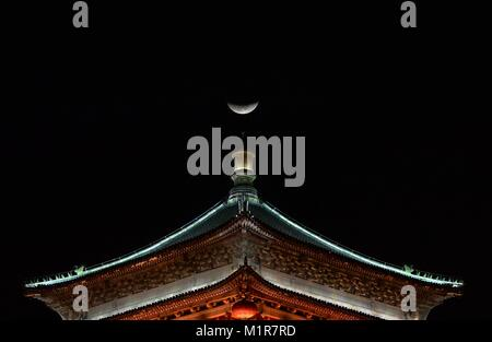 Xi'an. 31st Jan, 2018. Photo taken on Jan. 31, 2018 shows the moon seen from a bell tower in Xi'an, northwest China's - Stock Photo
