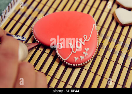 Gingerbread in the shape of heart decorated with red glaze with the inscription 'love'.  - Stock Photo