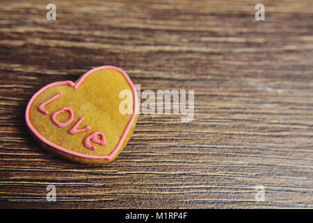 beautiful gingerbread in pink glaze in the shape of heart on a wooden background - Stock Photo