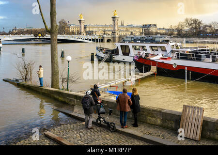 Onlookers observing the Seine in flood and the tricky situation of the houseboats docked at the Champs-Elysees port, - Stock Photo