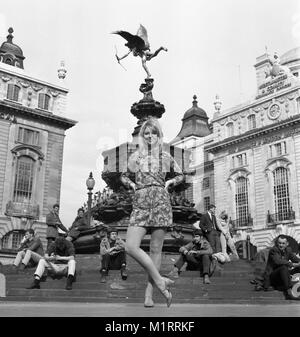 A model poses in a mini dress outdoors in London's Piccadilly near the statue of Eros in circa 1968 wearing a colourful mini-dress.   Photo by Tony Henshaw