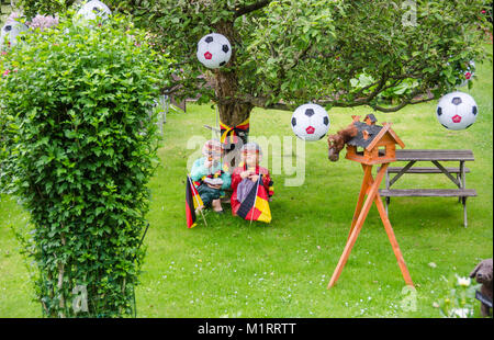 Berlin, Germany - July 2, 2016: German football fans decorated their garden with flags and balls looking forward - Stock Photo