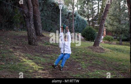 Child playing and sliding on a zip line between two trees in his garden - Stock Photo