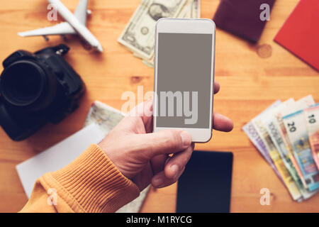 Travel app for mobile phone mock up screen, overhead view of male hand using smartphone with blank screen as copy - Stock Photo