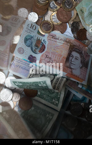 DONATIONS: Notes and coins of various currencies in a donation box - Stock Photo