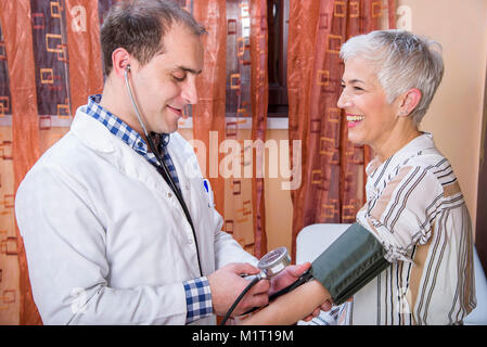 Senior woman checking her blood pressure at the clinic - Stock Photo