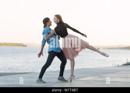 A slender ballerina dances with a modern dancer. Dating lovers. Passion and romance of dance. He holds her hand. - Stock Photo
