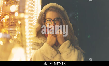 A young attractive hipster girl in glasses and a warm scarf walks by the mall on a holiday. She smiles and straightens - Stock Photo