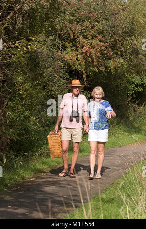 Elderly couple walking along the towpath of the Wilts and Berks canal near Swindon UK. - Stock Photo